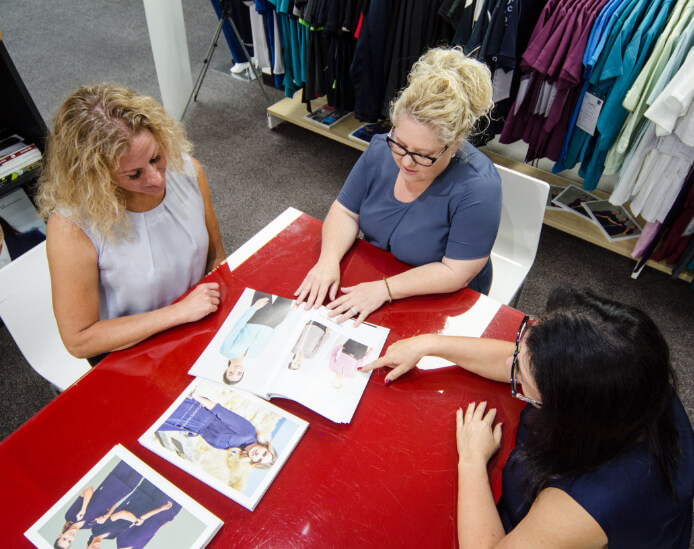 Women looking at uniform designs around a table