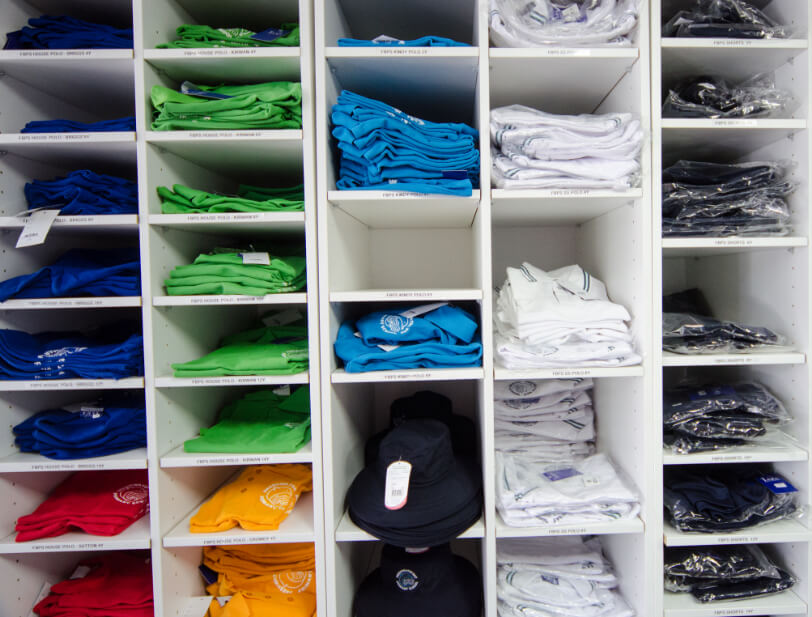 Different coloured uniforms folded on shelves