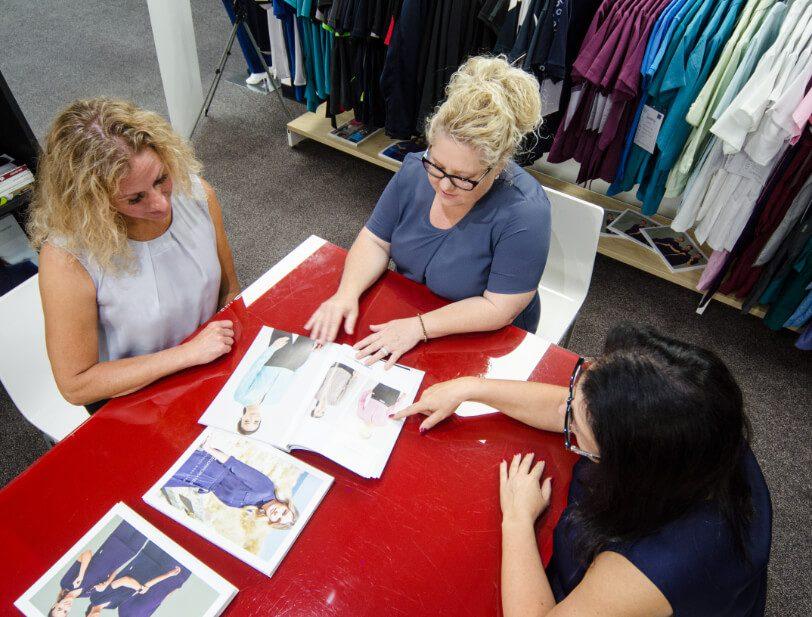 Tara Uniform design services. Consultants looking at uniform designs with customers.